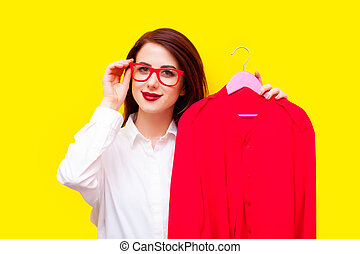 beautiful young woman with shirt on hanger standing in front of the wonderful yellow background
