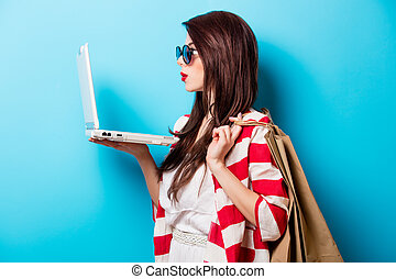 beautiful young woman with shopping bags and laptop standing in front of wonderful blue background