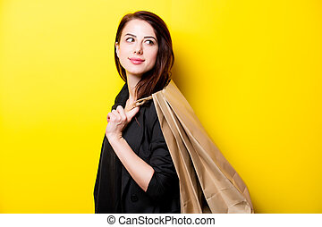 beautiful young woman with shopping bags standing in front of wonderful yellow background