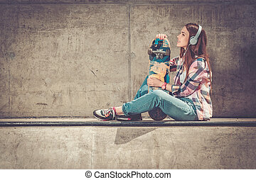 Beautiful young woman with skateboard outdoors