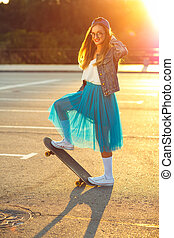 Beautiful young woman with skateboard, backlit at sunset -...
