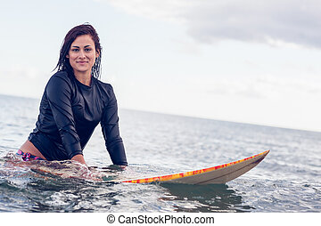 Beautiful young woman with surfboard in the water