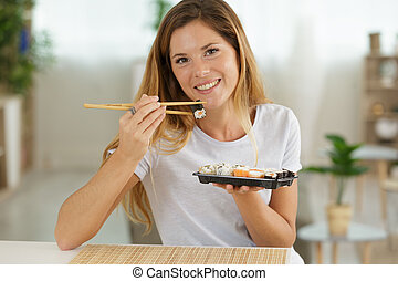 beautiful young woman with sushi roll at home