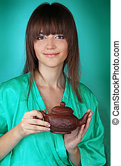 Beautiful young woman with teapot over green