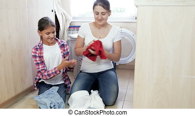 Beautiful young woman with teenage daughter doung housework in laundry