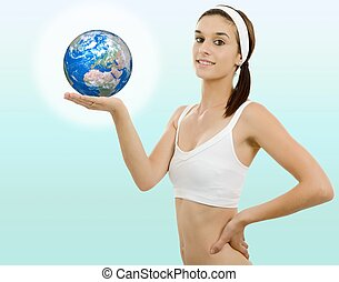 Beautiful young woman with the earth in hand