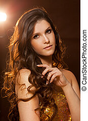 Beautiful young woman with wavy hair in golden dress.