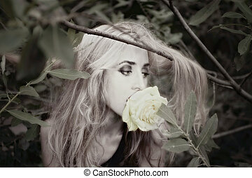 beautiful young woman with white rose in his mouth