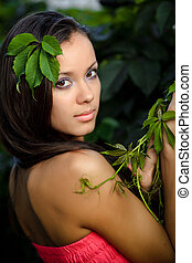 beautiful young woman with wild grape leaves