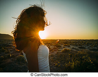 Beautiful young woman with wind in her hair at beach sunset.