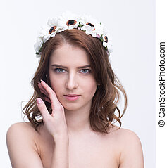 Beautiful young woman with wreath looking at camera