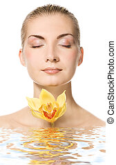 Beautiful young woman with yellow orchid reflected in rendered water