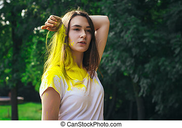 Beautiful young woman with yellow paint on her body