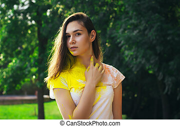 Beautiful young woman with yellow powder on her body