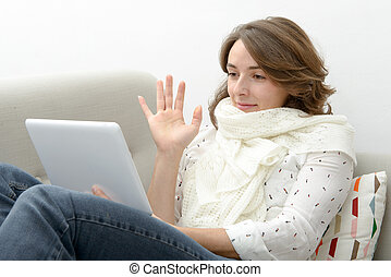 Beautiful young woman woman with a tablet in the sofa