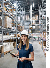 Beautiful young woman worker of furniture store in shopping center. Girl looking for goods with a tablet is checking inventory levels in a warehouse. Logistics concept