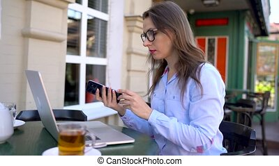 Beautiful young woman working and speaking on a smartphone...