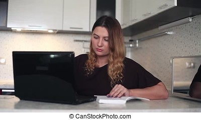 Beautiful young woman working at the computer with a diary.