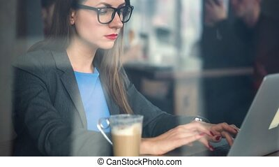 Beautiful young woman working in a cafe - modern business...