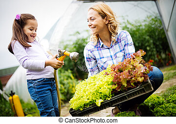 Beautiful young woman working in garden with her daughter