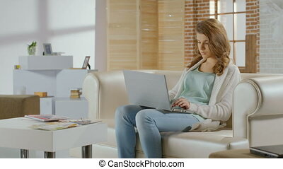 Beautiful young woman working on laptop in modern apartment