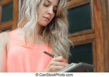 Beautiful young woman writes in a notebook.