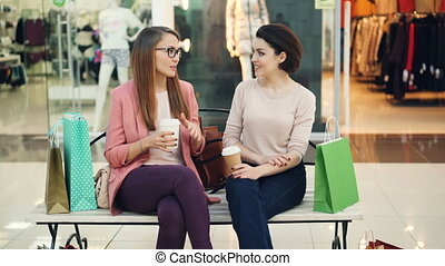 Beautiful young women are chatting in shopping mall holding...