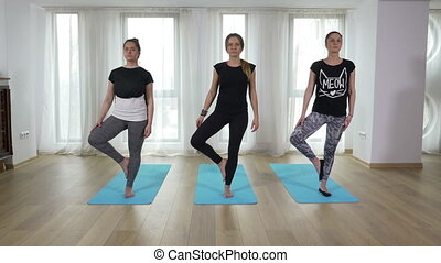 Beautiful young women standing in yoga pose tree asana