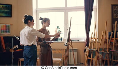 Beautiful young women student and professional artist are...