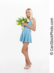 Beautiful young women with flowers. Attractive young woman holding a bunch of flowers while standing against white background