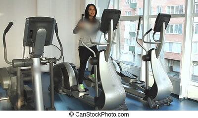Beautifull female during exercise on a elliptical traner