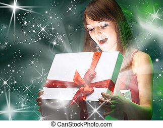 Beautifull girl opening x-mass magic present. Christmas