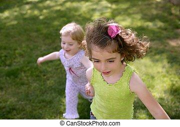 Beautifull little sisters running on the park