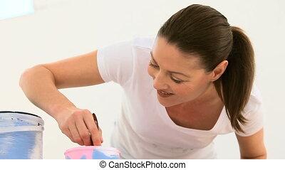 Beautifull woman painting a wall at home