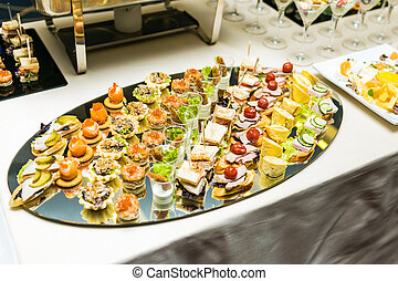 Beautifully decorated catering banquet table with different food snacks and appetizers with sandwich, caviar, canape on corporate event or wedding celebration