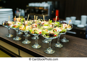 Beautifully decorated catering banquet table with different food snacks in a glass on corporate event or wedding celebration