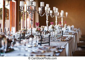 Beautifully decorated tables with candelabra at wedding reception, selective focus