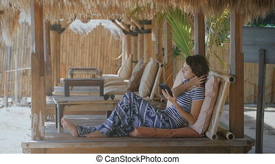 Beautifully dressed girl lying on a lounger on a tropical resort in Bali. Young woman uses tablet and smartphone while relaxing in the hotel.