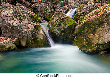 Beautifully flowing water between stones in the mountains, boulders covered with moss, beautiful nature