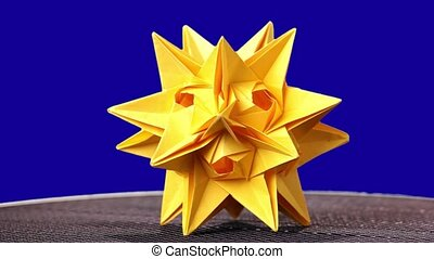 Beautifully folded kusudama figure. Yellow origami star on...