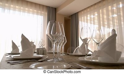 Beautifully served dining table in modern apartment. Wine glasses, plates, cutlery and napkins are on table.