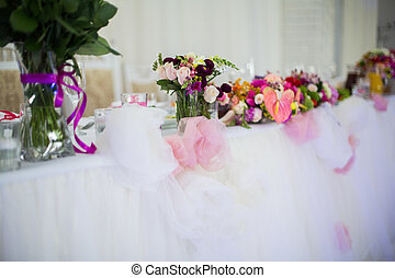 Beautifuly decorated wedding reception table covered with fresh flowers