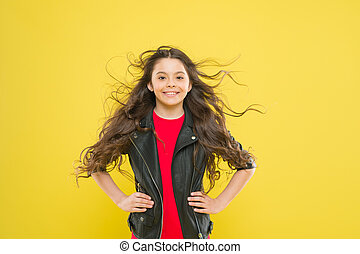 Beautify your hair today. Little kid with cute smile and wavy textured hair. Adorable small girl with long brunette hair smiling with fashion look. Happy child with flowing hair on yellow background
