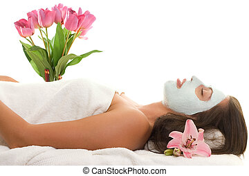 A relaxed young woman with a treatment facial.