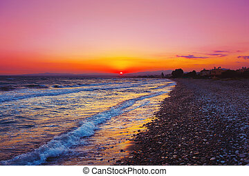 Beautuful sunset over Mediterranean sea. Cobble stone beach.