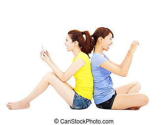 beautuful  young woman playing smart phone on a floor