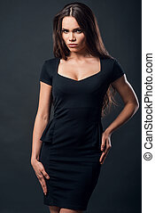 Beauty and confidence. Attractive young woman in black dress holding hand on hips and looking at camera while standing against black background