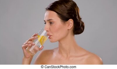 woman drinking fresh water with lemon slices - beauty and ...
