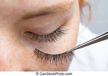 Beauty and fashion concept - Eyelash Extension Procedures. Closed eye Red-haired girl with freckles Model with Long artificial Eyelashes on tweesers.