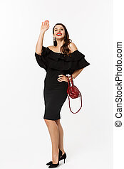 Beauty and fashion concept. Full length of attractive young woman in black dress and makeup, saying hello and smiling, waving hand to greet, white background